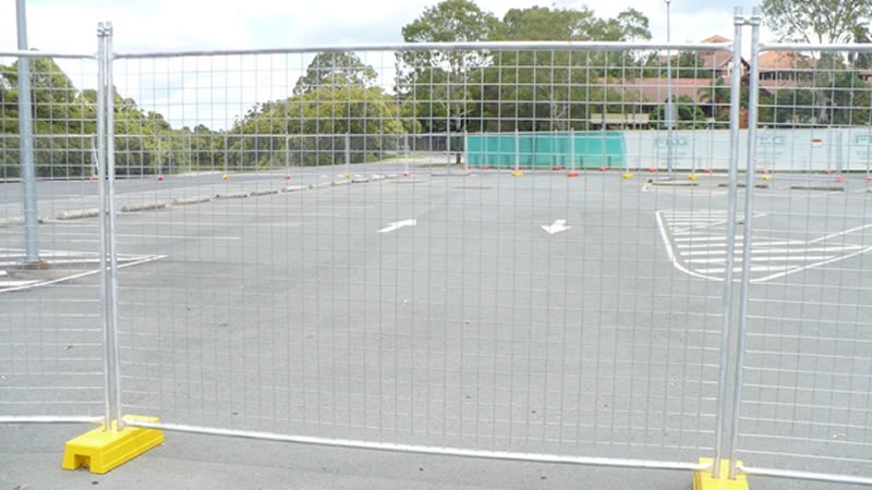 a galvanized australia temporary fence installed with the yellow plastic moulded feet standing on the concrete