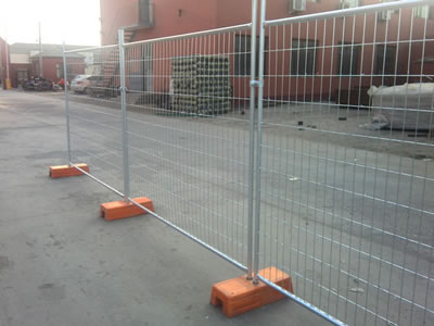 Three galvanized welded temporary fencing on the ground. They are connected by clamps and orange plastic moulded feet.