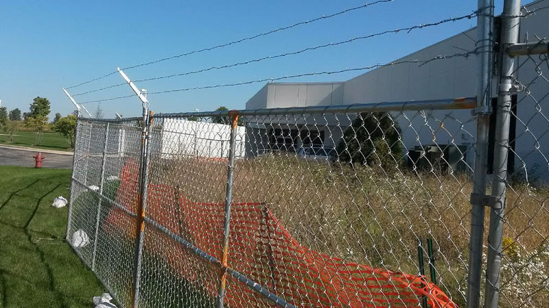 Barbed wire is fixed on the chain link temporary fence and an orange warning barrier fence is fastened on the fence.