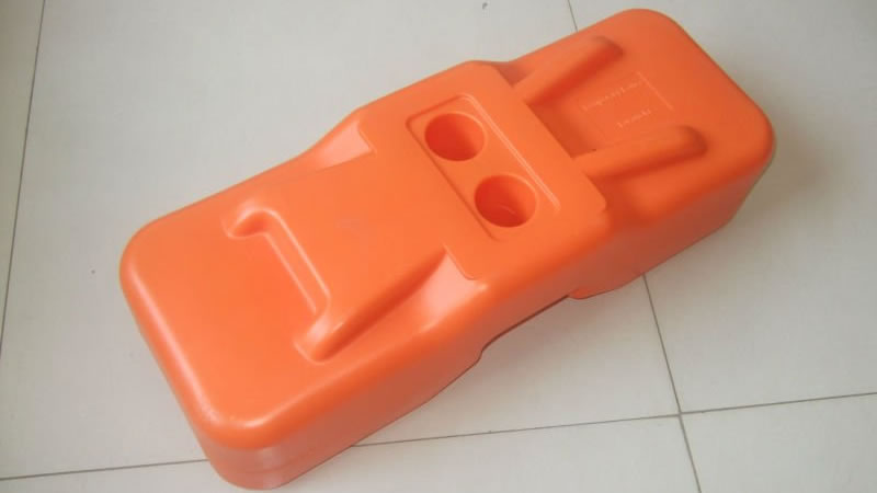 An orange blow moulded temporary fence feet on the floor.