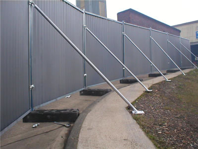 The straight steel bracing supports the temporary hoardings.