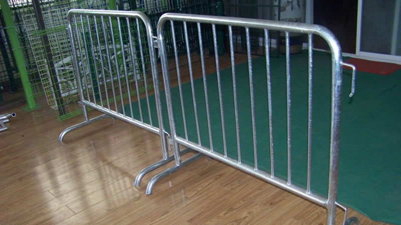 Two crowd control barriers with bridge feet are standing on the floor.