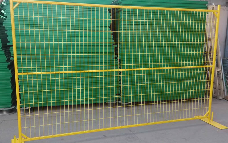 A Canada type temporary fencing on the ground with several green panels behind of it.