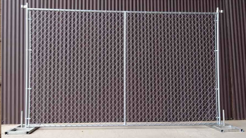 a chain link temporary fence panel is standing next to the hoarding the panel has