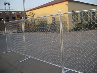 Galvanized chain link temporary fence stands on the ground of the factory.