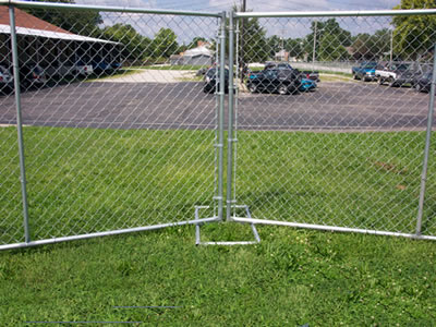 A part of chain link temporary fencing which is installed on lawn. Many cars parked on the ground that next to the lawn.