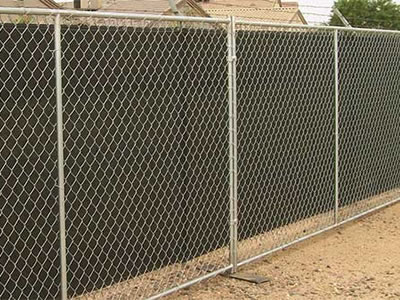 Chain link temporary fence supported by flat metal feet in residential areas. The fence is installed with shade cloth.