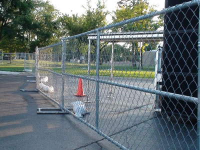 Galvanized chain link temporary fencing erected around a construction site.