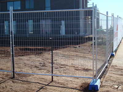Around a construction site, the square top welded temporary fence is installed to separate the building and the road.