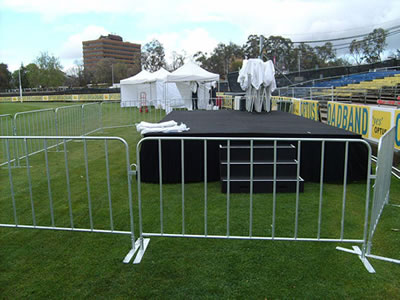 Crowd control barriers with flat feet are installed around a black performance stage and some tools.