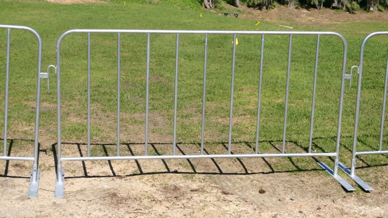 Three pedestrian barrier panels installed with flat feet stand on the lawn, they are interlocked with hook and loop.