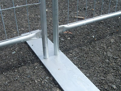 A flat galvanized temporary fence steel feet is installed with two welded temporary fence panels.