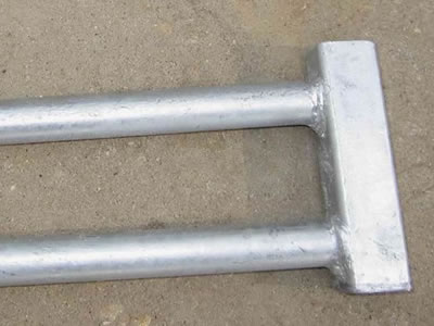 A galvanized Canada temporary fence clamp on the ground.