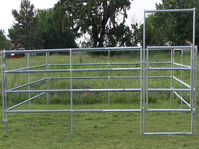 The galvanized corral panel with a gate stands on the lawn. The gate is installed with the fence panels with clamps.