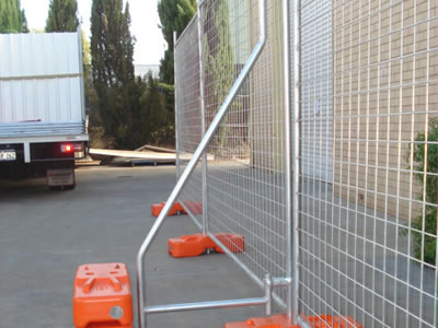 A steel temporary fence bracing supports the temporary fence with three orange plastic moulded feet installed.