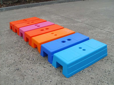 Seven injection moulded temporary fence feet on concrete. Their colors are light blue, dark blue, orange and purple.