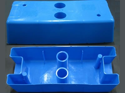 Two blue injection moulded temporary fence feet on the floor. We can see their positive and back sides.