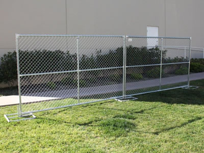Two large size chain link temporary fences on the lawn. The fence panels have cross reinforced pipes.