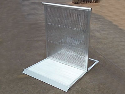An aluminum stage barrier on the ground with perforated sheet front panel.