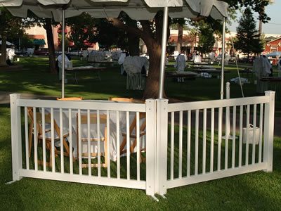 Two traditional type event fencing panels install next to the chairs and desks. A tent is set up next to them.