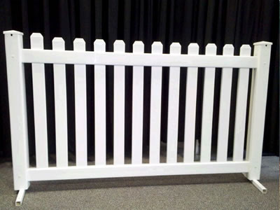 A white picket event fencing panel on concrete.