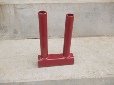 A PVC coated Canada temporary fence clamp on the concrete and it is painted with red.