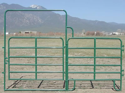 A green PVC coated corral panel gate stands on the ground. The gate frame is welded onto the panel.