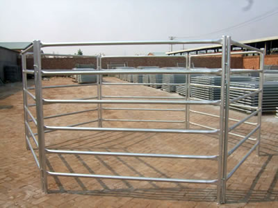 A corral fence stands on the ground of factory. The fence panels with round frame and six round horizontal tubes.