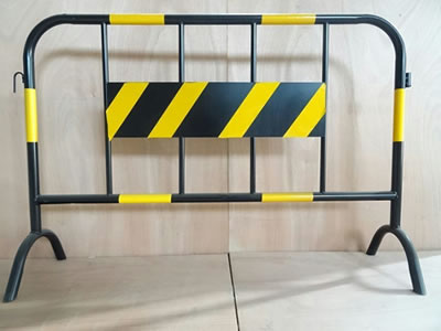A black and yellow road safety barrier stands on the floor, a metal board are welded at the infilled pipes.