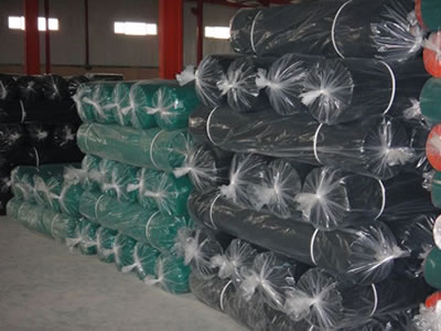 Many green and black shade cloth rolls on the ground, they all packaged with plastic film.