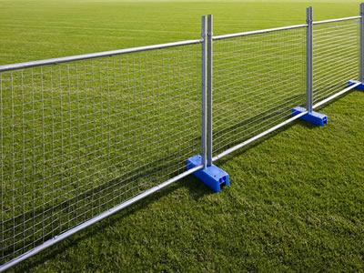 The galvanized temporary fence is erected on the lawn, it has square top and blue plastic moulded feet.