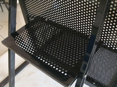 A black powder coated stage barrier has a foot board at the back of the front panel.