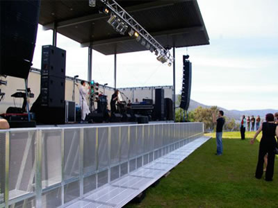 A long row of aluminum stage barrier is installed before the performance stage.