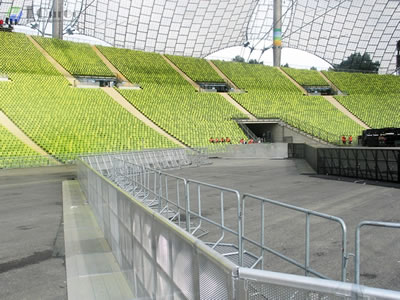 Two long rows of stage barriers parallel to police barrier, they serve as a barricade together in sport venue.