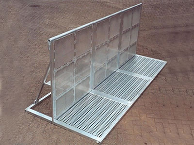 An aluminum stage barrier on the ground with extended front board supporting.