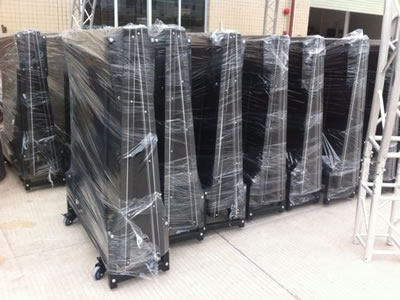 Many folded stage barriers are packaged with the plastic film and they are standing on the floor.