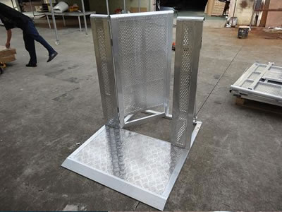 An aluminum stage barrier gate on the ground and its door is opening.