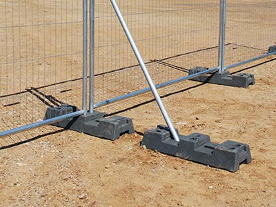 A steel temporary fence bracing supports the temporary fence with a black rubber feet installed.