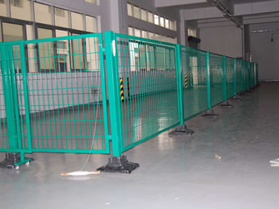 Green powder coated welded temporary fence with a sliding gate is erected in a room. The plastic base is black.