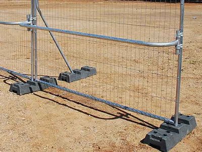 Welded temporary fence is supported by black rubber feet and brace. A handrail installs at the middle of fence.