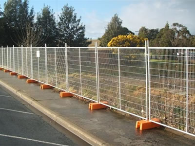 Galvanized welded temporary fencing is supported by orange plastic moulded feet at roadside.