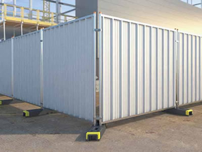 The corner of temporary hoardings in a constructions site. The hoardings are installed with plastic feet.