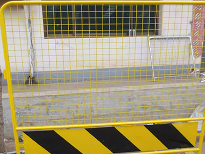 A yellow road barrier in the yard. The barrier has round top and a yellow and black signage under infilled welded mesh.