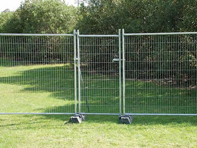The pedestrian temporary fence gate is installed with the temporary fence panels in a greenbelt.
