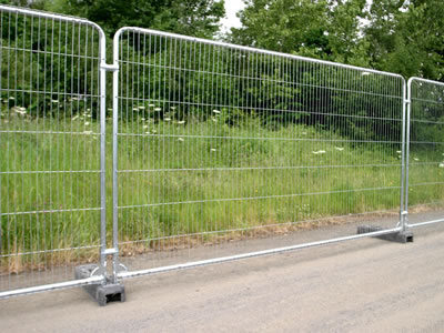 A galvanized temporary fence at roadside. The fence with gray rubber feet has round top.